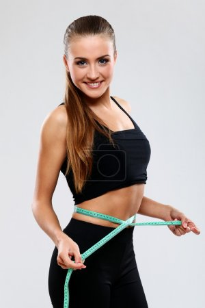 Happy girl measuring her waist with a ruler