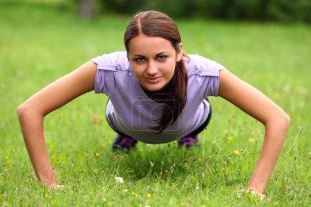 Foto de Joven y linda chica deportiva hacer sus ejercicios de flexiones de brazos en el parque en un prado verde - Imagen libre de derechos