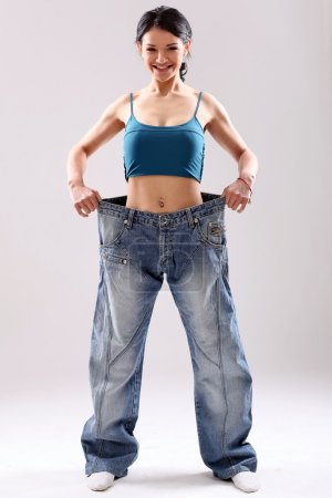 Cute slim girl wearing old jeans after weight loss