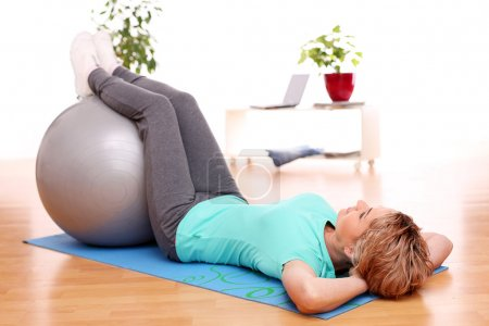 Slim mid aged woman do exercises with ball