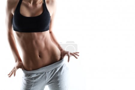 Photo for Sexy sporty woman with slim stomach over a white background - Royalty Free Image
