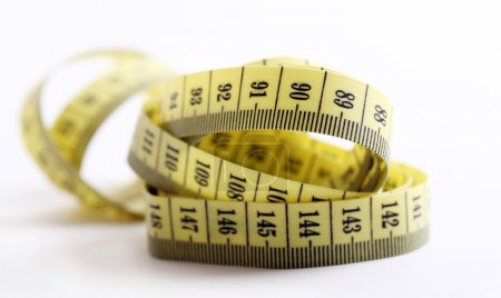 Yellow measure tape over white background