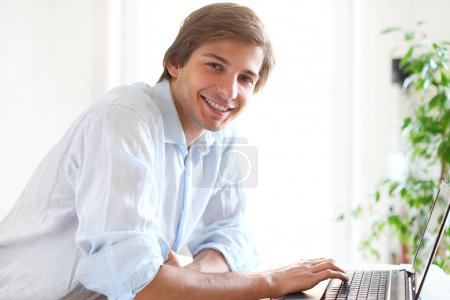 Handsome man smiling and working on laptop