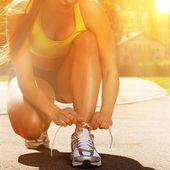 Beautiful woman in fitness wear ties shoelaces