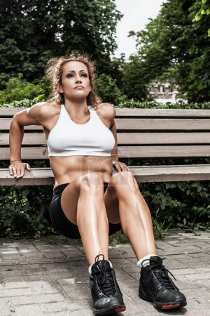 Fitness girl is working out in the park