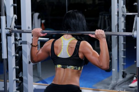 Muscular beautiful woman at a gym