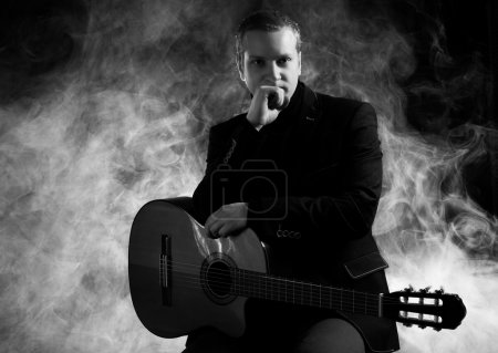 Photo for Music. Young musician in black suit holding a guitar - Royalty Free Image