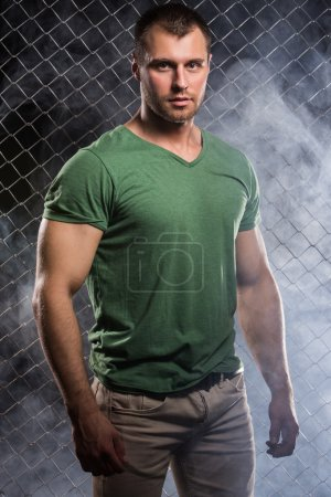 Photo for Fitness. Beautiful, strong man in clothes on fence background - Royalty Free Image