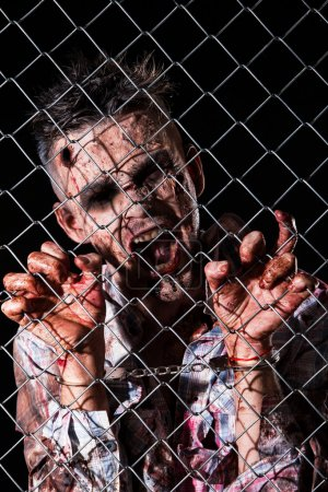 Scary zombie behind the fence