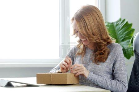 Photo pour Mode de vie, livraison, courrier. belle femme avec le paquet sur la table au bureau - image libre de droit