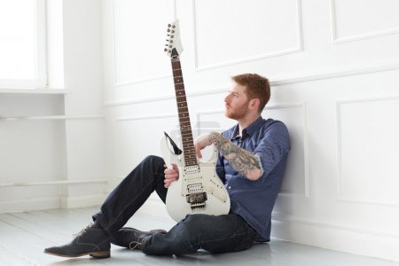 Photo for Handsome guy on the floor with electric guitar - Royalty Free Image