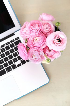 Photo for Beautiful pink roses bouquet in the pot with laptop - Royalty Free Image