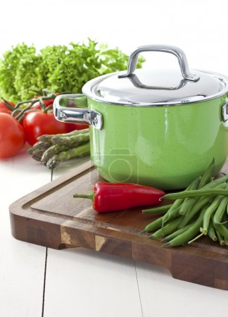 Green cooking pot and vegetables