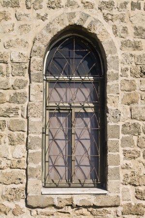 Photo pour Fenêtre voûtée antique dans un mur de pierre - image libre de droit
