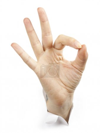 Fingers showing ok sign bursting through paper