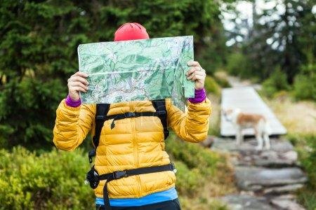 Frau wandert und liest Landkarte im Wald