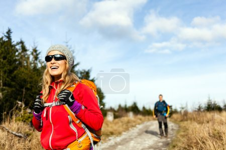 Photo for Man and woman hikers hiking on mountain trail autumn or winter nature. Young couple backpackers walking in forest, Poland. - Royalty Free Image