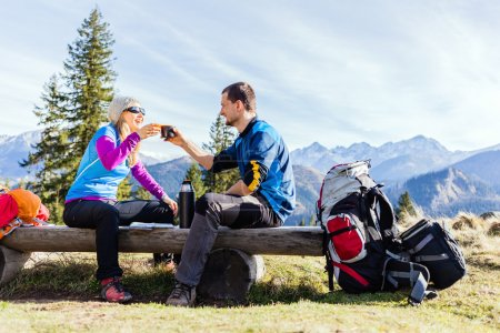 Couple hikers camping and drinking in mountains