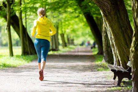 Photo pour Femme coureuse courant et marchant dans le parc, nature estivale, faisant de l'exercice dans une forêt lumineuse à l'extérieur - image libre de droit