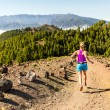 Young woman cross country running in mountains on ...