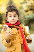 Funny little girl with ice-cream in autumn forest