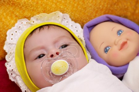 Cute funny infant baby with doll