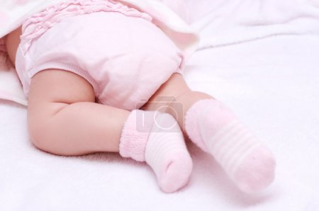 Newborn baby girl feet in pink socks...