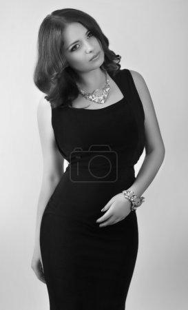 Photo pour Belle jeune femme en robe noire avec bracelet et collier dans un style rétro - image libre de droit