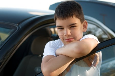 Photo for Image of a cute young boy standing near a black car - Royalty Free Image