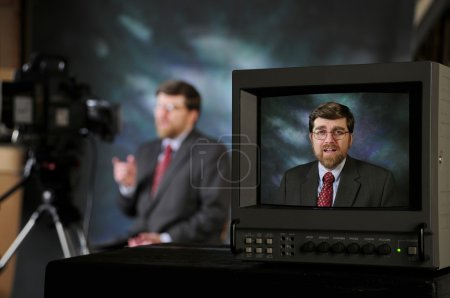 Monitor in TV production studio showing man talking to a camera