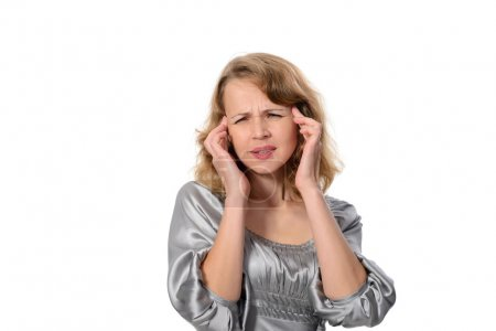 Woman suffering from a headache grimacing and holding her hands to her ears