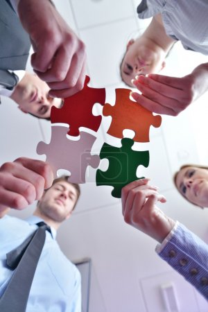 Group of business assembling jigsaw puzzle