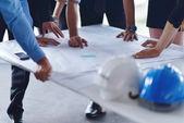 Business-Menschen und Bau-Ingenieure treffen