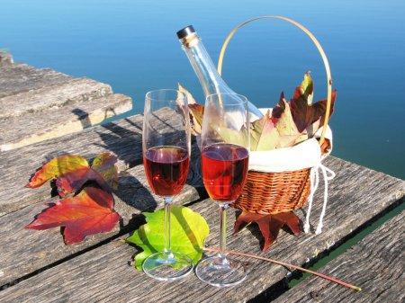 Photo pour Deux verres à vin sur une jetée en bois - image libre de droit