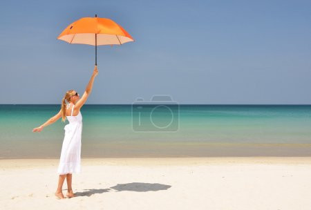 Girl with an orange umbrella on the tropical beach