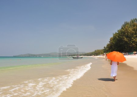 Girl with an orange umbrella on the beach of Phuket island