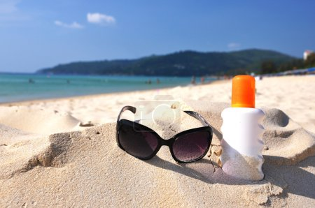 Sunglasses and lotion on the sandy beach of Phuket island, Thail