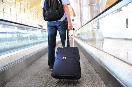 voyageur avec une valise sur le speedwalk