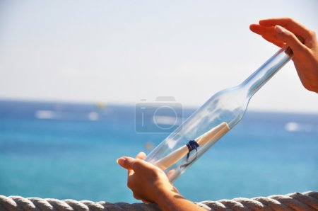 Photo for Bottle with a message in the hands - Royalty Free Image