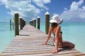 Dívka na dřevěné molo na oceánu. Exuma, Bahamy