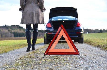 Photo pour Voiture cassée, fille et triangle d'avertissement - image libre de droit