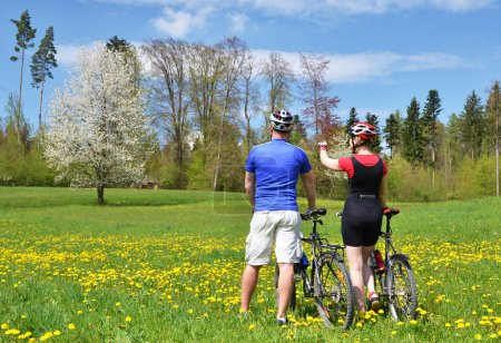 Photo for Travelers with mountain bikes in a meadow - Royalty Free Image