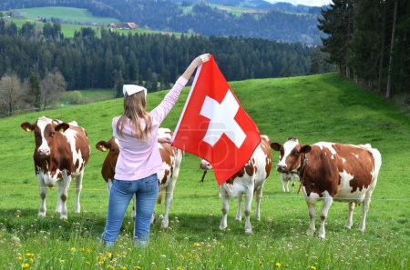 Girl with the Swiss flag against cows.