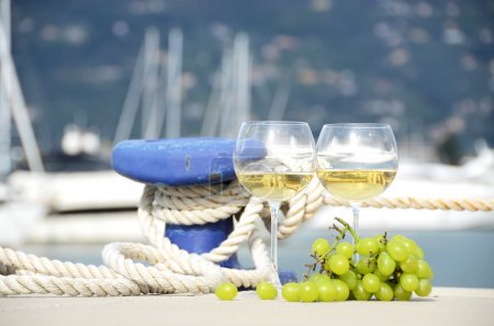 Wineglasses and grapes on the yacht pier