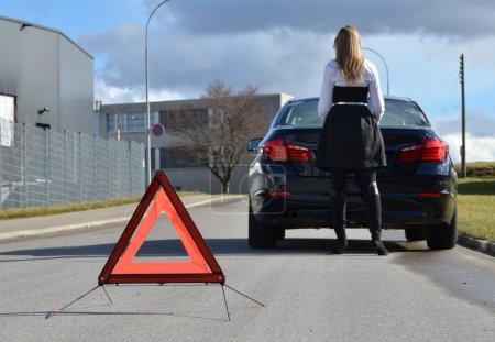 Photo pour Femme debout à la voiture cassée sur la route - image libre de droit