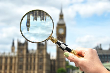 Magnifying glass in the hand against Big Ben