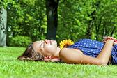 Mladá dívka leží na zelené trávě