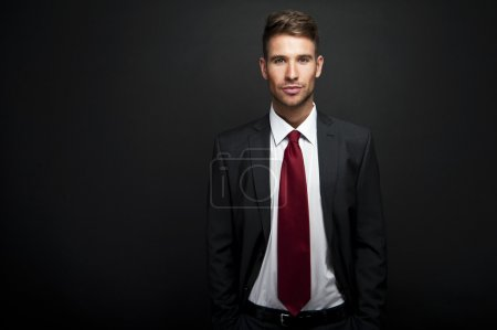 Businessman standing on dark gradient background