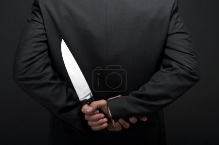 Businessman with knife behind his back