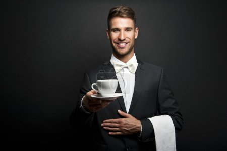 Waiter in suit holding coffee cup